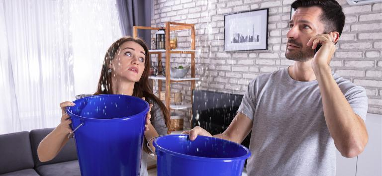 https://pipeitup.com/wp-content/uploads/2021/03/couple-using-bucket-for-collecting-water-leakage-from-ceiling-picture-id1145766999-1.jpg